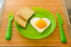 Fried egg in the shape of heart Stock Photos