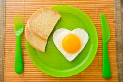 Fried egg in the shape of heart Stock Photography
