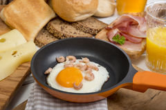 Fried egg with shrimps in pan, cheese, ham, bread and buns Royalty Free Stock Image