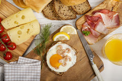 Fried egg with shrimps on protein bread, cheese, ham, juice Royalty Free Stock Photos