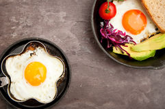 Fried egg on skillet. Breakfast skillet pan of fried egg, avocado and tomato. Served on a gray stone slate background Royalty Free Stock Photos