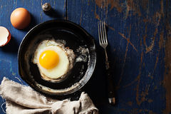 Fried egg in a skillet. Old-fashioned fried egg in a cast-iron skillet on wooden background Stock Photography