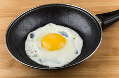 Fried egg in small pan with handle on board Royalty Free Stock Image
