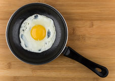 Fried egg in small pan with handle on board Royalty Free Stock Photography