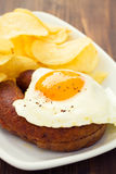Fried egg with smoked sausage. And chips Stock Images
