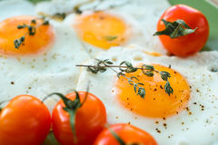 Fried egg, spices and cherry tomatoes. Delicious and healthy breakfast. Sunny side up. Selective focus Stock Image