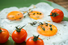 Fried egg, spices and cherry tomatoes. Delicious and healthy breakfast. Sunny side up. Selective focus Royalty Free Stock Photography