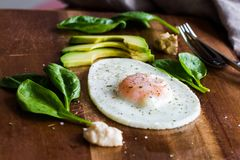 Fried egg with spinach, avocado and hummus Stock Photo