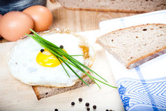 Fried egg sunny side up on slice of bread with parsley and pepper Royalty Free Stock Photo