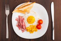 Fried egg with toasts, ham and cherry tomato Stock Photos