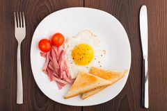 Fried egg with toasts, ham and cherry tomato Stock Photography