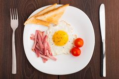 Fried egg with toasts, ham and cherry tomato Stock Images