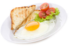 Fried egg with toasts and vegetables Royalty Free Stock Images
