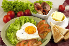 Fried egg, tomato and bacon Stock Images