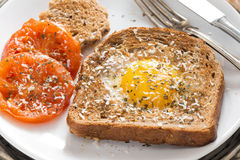 fried egg and tomatoes in a toast for breakfast, close-up Stock Photo