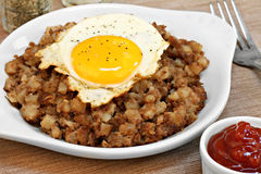 Fried egg on top of roast beef hash. Royalty Free Stock Photo
