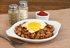 Fried egg on top of roast beef hash. Stock Photos