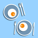 Fried egg Vector illustration. Two servings of fried eggs in plates with cutlery on a blue background Flat design Royalty Free Stock Photography