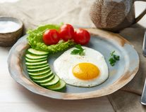 Fried egg, vegetables. Paleo, keto, fodmap diet. Copy space, side view. Healthy diet concept, blue plate on white wooden table royalty free stock photos