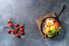 Fried egg with vegetables. Traditional Israeli Cuisine dishes Shakshuka. Fried egg with vegetables tomatoes and paprika in cast-iron pan on wooden board with Royalty Free Stock Photos