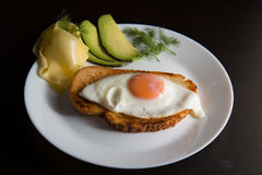 Fried egg. On white plate with avocado cheese and bread Stock Images