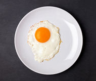 Fried egg in a white plate on the black background Royalty Free Stock Photos