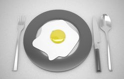 Fried egg in white plate with fork and knife on the table Stock Photo
