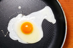 Fried egg on a yellow background with black pepper Stock Photos