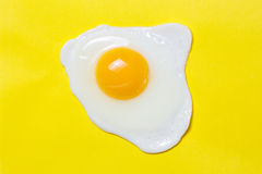 Fried egg on a yellow background with black pepper Royalty Free Stock Image