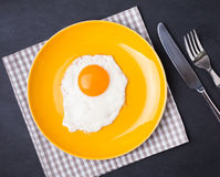 Fried egg on the yellow plate Stock Images
