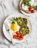 Fried egg, zucchini fritters and cream cheese sandwich - delicious breakfast, brunch or snack. On a light background. Top view Stock Images