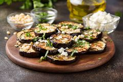 Fried eggplant with feta, pine nuts, fresh herbs (cilantro, parsley) and olive oil. Tasty vegetable snack, summer, spring food,. Picnic stock photo