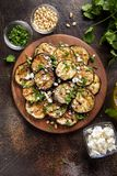 Fried eggplant with feta, pine nuts, fresh herbs (cilantro, parsley) and olive oil. Tasty vegetable snack, summer, spring food,. Picnic royalty free stock image