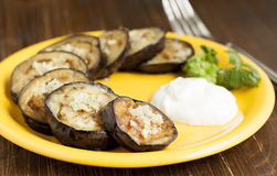 Fried eggplant with garlic   on a yellow plate. Stock Photo