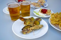 Fried eggplants rolled up with shrimps inside, two beers royalty free stock photography