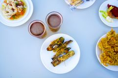 Fried eggplants rolled up with shrimps inside, two beers and oth stock photography