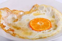 Fried eggs. With an orange segment instead of a yolk, symbolising healthy food royalty free stock photography
