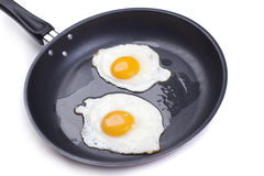Fried eggs. Fried egg on a frying pan isolated on white background royalty free stock image