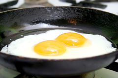 Fried eggs. Two fried eggs in hot pan on gas stove Stock Photos