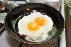 Fried eggs. Two fried eggs in hot pan on gas stove Royalty Free Stock Photos