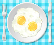 Fried eggs. On your plate with knife and fork Royalty Free Stock Image