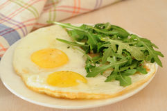 The fried eggs with arugula, orange juice, croissant, continental breakfast concept Stock Image