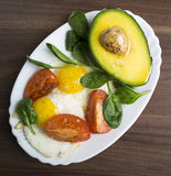 Fried eggs with avocad. O, spinach and tomatoes Stock Photo