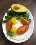 Fried eggs with avocad. O, spinach and tomatoes Royalty Free Stock Photography