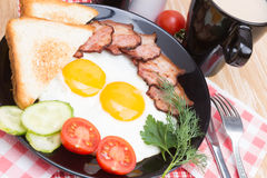 Fried eggs with bacon on black dish Royalty Free Stock Photos