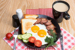 Fried eggs with bacon on black dish Royalty Free Stock Image