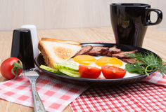 Fried eggs with bacon on black dish Stock Photo