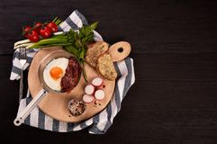 Fried eggs with bacon on a board in a pan stock photography