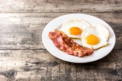 Fried eggs and bacon for breakfast on wood. En table. Copyspace stock photography