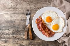 Fried eggs and bacon for breakfast on wood. En table. Top view. Copyspace royalty free stock image